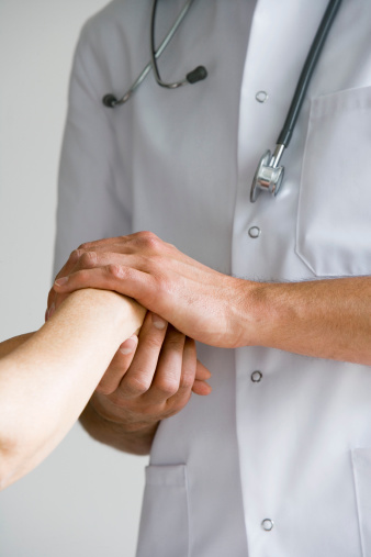 Doctor holding woman's hand