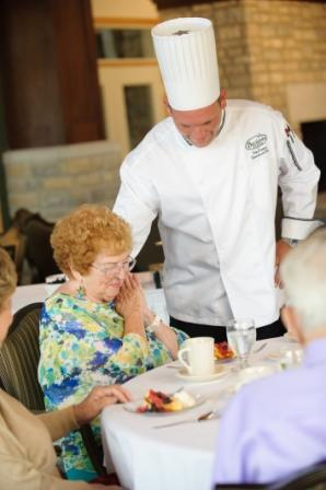 Chef serving older woman