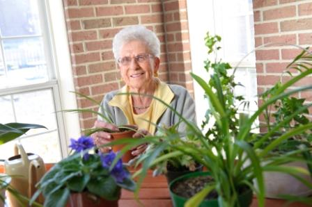 Older woman behind flower pots